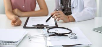 De stethoscoop, medische voorschriftvorm ligt tegen de achtergrond van een arts en een geduldig het bespreken gezondheidsexamen stock afbeeldingen