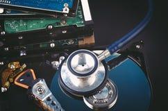 De stethoscoop op stoffig ontmantelt harde schijf over donkere achtergrond royalty-vrije stock foto's