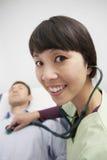 De Stethoscoop van artsenexamining patient with Stock Foto
