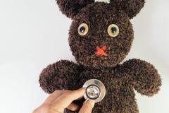 De stethoscoop van de de handholding van de arts zette op leuke bruine met de hand gemaakte pluizige pop met pitty ogen, gezondhe royalty-vrije stock foto's
