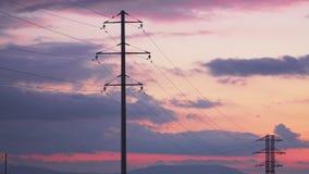 De steun met hoog voltage bij zonsondergang, de vogelsvlieg en zit op hen stock videobeelden