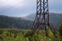 De steun van de machtslijn in bergen in bewolkt weer stock foto's