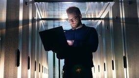 IT de steuningenieur in glazen stelt laptop in een serverruimte in werking stock video