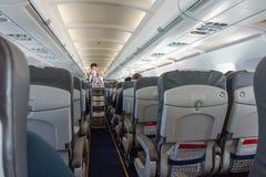 De stewardess biedt voedsel en dranken aan passagiers uit de toeristenklasse aan royalty-vrije stock foto's