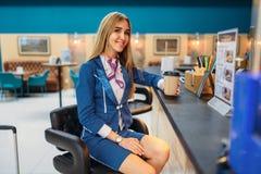 De stewardess drinkt koffie in luchthavenkoffie stock foto