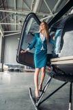 De stewardess in eenvormig stelt tegen helikopter stock afbeelding