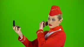 De stewardess kijkt in de spiegel en schildert haar gezicht met een leeswijzer Het groene scherm stock footage