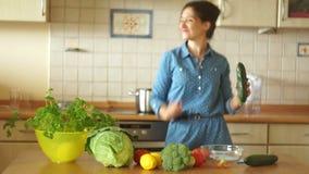 De stewardess treft in de keuken in een mooie stemming voorbereidingen Een meisje snijdt een komkommer en danst aan muziek stock video