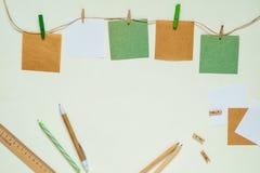 De stickers van kraftpapier en van het Witboek met wasknijpers op een kabel stock foto's
