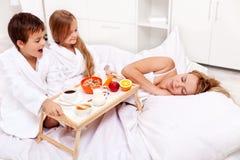 De stijging en glanst - ontbijt in bed voor mamma Stock Foto's