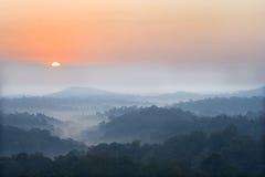 De stijging van de zon boven een mist en een berg Stock Foto