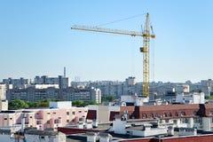 De stijgingen van de de bouwkraan boven de daken van gebouwen met meerdere verdiepingen royalty-vrije stock foto