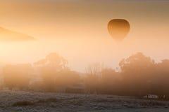 De Stijgingen van de hete Luchtballon door de Mist Royalty-vrije Stock Afbeelding
