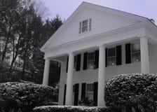 De stijlwit huis van New England met veelvoudige kolommen en Kerstmiskaarsen in venster Royalty-vrije Stock Foto
