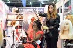 De stilist bij het haar maakt tot het haar zwarte modellen bij het festival royalty-vrije stock fotografie