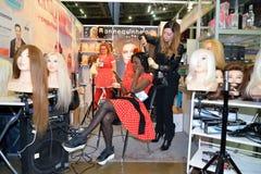 De stilist bij het haar maakt tot het haar zwarte modellen bij het festival stock fotografie