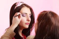 De stilist die van de make-upkunstenaar oogschaduw op ooglid van vrouw toepassen royalty-vrije stock afbeelding