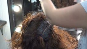 De stilist-kapper past verf op het haar van een meisje van Oostelijke nationaliteit tijdens de procedure van haar toe die binnen  stock video