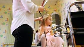 De stilist krult lang haar voor weinig leuk meisje, gebruikend elektrisch krullend ijzer Sluit omhoog van het krullen van ijzer stock footage