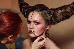 De stilist maakt Halloween-make-up, borstelend bloed op modellenlippen stock fotografie