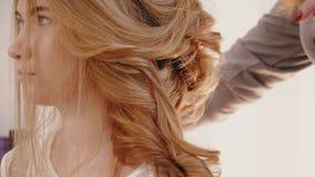 De stilist maakt het kapsel van de blondebruid stock video