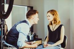 De stilist maakt jong meisje tot professionele make-up stock foto