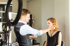De stilist maakt jong meisje tot professionele make-up royalty-vrije stock afbeelding
