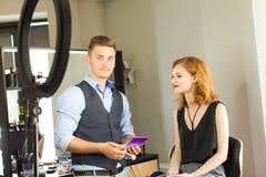 De stilist maakt jong meisje tot professionele make-up royalty-vrije stock afbeeldingen