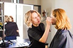 De stilist maakt jonge meisjesberoeps omhoog maken stock fotografie