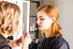 De stilist maakt jonge meisjesberoeps omhoog maken royalty-vrije stock afbeelding