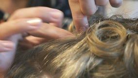 De stilist maakt krullen aan aantrekkelijke bruin-haired stock videobeelden
