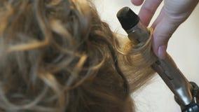De stilist maakt krullen bruin-haired gebruikend het krullen stock videobeelden