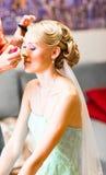 De stilist maakt make-upbruid op de huwelijksdag stock afbeelding