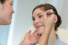 De stilist maakt make-upbruid op huwelijksdag royalty-vrije stock foto's