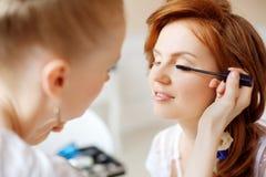 De stilist maakt make-upbruid vóór het huwelijk stock fotografie