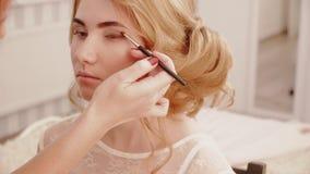 De stilist maakt ogen tot make-up aan het meisje van de blondebruid stock videobeelden