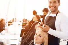 De stilist past hairspray op blond haar van het rijpe vrouw kijken in spiegel toe royalty-vrije stock foto's