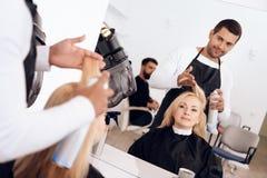 De stilist past hairspray op blond haar van het rijpe vrouw kijken in spiegel toe royalty-vrije stock foto