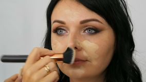 De stilist past stichting op het gezicht van vrouwenmodel in toe een schoonheidssalon, die samenstelling gelijk maken stock footage