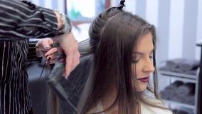 De stilist werkt met het haar van een mooi jong meisje stock footage