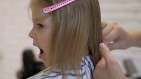 De stilistkapper maakt een kapsel voor een leuk meisje in een schoonheidssalon Het kappen, haarknipsel stock videobeelden