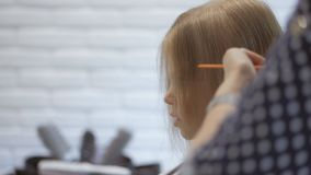 De stilistkapper maakt een kapsel voor een leuk meisje in een schoonheidssalon Het kappen, haarknipsel stock video