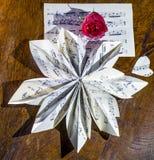 De stillevensamenstelling met een muzikale die score wordt in de vorm van een bloem en een rood wordt gevouwen gemaakt dat nam to royalty-vrije stock afbeelding