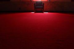 De stoel in dark op het rode tapijt Stock Fotografie