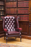 De stoel van Chesterfield in de bibliotheek Stock Afbeeldingen
