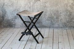 De stoel van de directeur op concrete muurachtergrond Zolderruimte Houten Vloer Daglicht Vrije ruimte voor tekst stock afbeelding