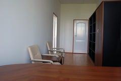 De stoelen en het bureau van het bureau stock afbeeldingen