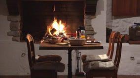 De stoelen en de lijst dichtbij open haard, heerlijke maaltijdvoorbereiding, wachten op minnaarspaar, romantisch diner, uitsteken stock footage