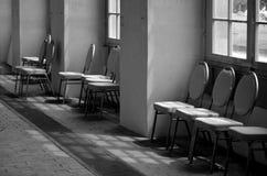 De stoelen onder squered venster stock fotografie