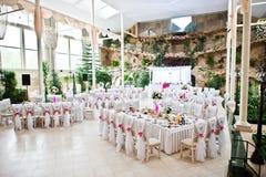 De stoelen van de huwelijksgast met roze linten bij huwelijkszaal Royalty-vrije Stock Afbeelding